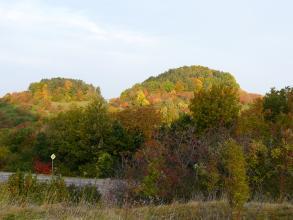 Blick auf zwei bewaldete, unterschiedlich hohe Berge, die hinter einem im Schatten liegenden Wald hervortreten.