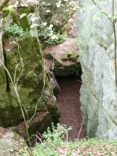 Blick von oben über eine Felskante in eine enge Kluft, die von hohen, links und rechts aufsteigenden Felswänden gebildet wird. Das Gestein links ist stark bemoost, rechts ist es ohne Bewuchs.