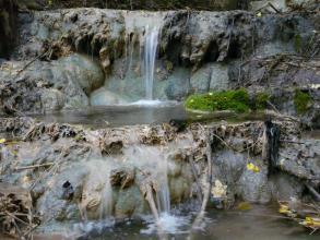 Blick auf einen schmalen Wasserfall, der über rundes, ausgewaschenes Gestein zuerst in ein kleines Becken und dann über eine zweite Terrasse im Vordergrund weiter abwärts fließt.