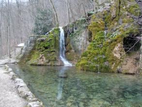 Blick auf eine nach links abfallende, bemooste und verwitterte Felsformation, über deren unteres Ende ein schmaler Wasserfall rinnt. Sein Wasser fließt in ein von Steinen eingefasstes klares Becken im Vordergrund.