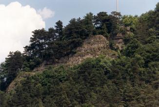 In einer Lücke zwischen sonst dichtstehender Bewaldung eines Berghanges zeigt sich eine graue, oben abgerundete Felswand. Nach links unten verliert sich das Gestein in einer dünnen, nur noch schwer zu erkennenden Linie.