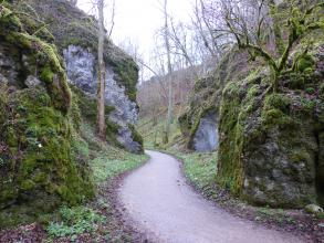 Das Foto zeigt zwei massige Felsböschungen, die sich gegenüberstehen. Ein schmaler Weg schlängelt sich zwischen den Felsen hindurch.