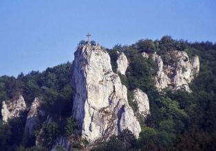 Blick auf markante, weißlich graue Felsen, die aus einem bewaldeten Berghang aufragen. Der vorderste und höchste der Felsen trägt ein Gipfelkreuz.