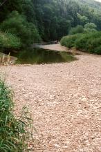 Blick auf einen Fluss, der nur im hinteren Teil Wasser führt. Im Vordergrund ist das Flussbett ausgetrocknet.