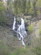 Aus einiger Entfernung blickt man hier auf einen Wasserfall, der sich aus großer Höhe über Felsstufen nach unten stürzt. Der oben aus zwei Strömen bestehende Wasserfall ist ringsum von Wald umgeben.