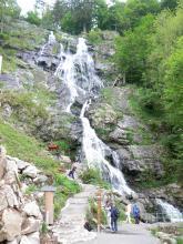 Blick auf eine hohe, abgestufte Felswand, über die ein breiter Wasserfall stürzt. Auf einem Treppenweg links steigen Besucher hinauf. Rechts wachsen Bäume am Felshang.