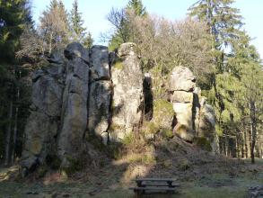 Die Aufnahme zeigt eine vor hohen Bäumen stehende Felsgruppe. Die Felsen bestehen aus sieben einzelnen Säulen, die sich aneinander lehnen. Das Gestein ist hellgrau und teilweise bewachsen. Der linke Teil der Gruppe liegt im Schatten.