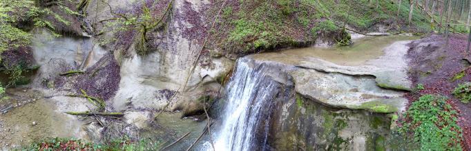 Panoramabild, das einem von rechts kommenden, an einem Waldhang entlangführenden Flusslauf bis zu einem Wasserfall in der Bildmitte folgt. Links des Falles fließt das Gewässer an einer Gesteinswand vorbei.