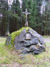 Im Mittelpunkt des Bildes steht ein großer, einzelner grauer Felsblock. Der Block liegt auf einer freien Fläche und trägt ein Heiligenblid mit Kruzifix. Hinter dem Findling steht Wald.