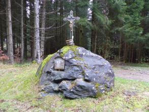 Das Foto zeigt einen größeren, abgerundeten Felsblock. Der blaugrau gefärbte Fels liegt auf einer freien, grasigen Fläche. Ein Kreuz sowie ein Heiligenbild sind auf ihm angebracht. Im Hintergrund steht Wald.