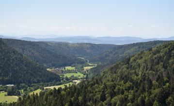 Blick aus großer Höhe in ein kleines, teilweise besiedeltes Tal. Zu beiden Seiten sowie am Ende des Tales steigen bewaldete Berghänge auf. In der Ferne sind weitere, höhere Berge zu erkennen.