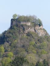 Aus dichtem Mischwald ragt ein kegelförmiger Felsenberg hervor, dessen Krone von Mauerresten umgeben sowie von Bäumen bestanden ist. Das offen liegende Gestein - auf der rechten Seite sichtbar - ist grau mit rötlich braunen Stellen.