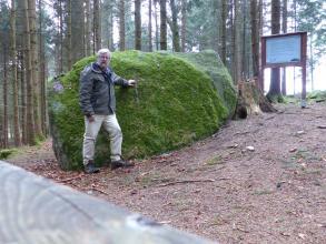 Blick auf einen fast zwei Meter hohen, rechteckigen bemoosten Felsblock, der auf einem leicht nach rechts ansteigenden Hang liegt. Ein Mann in grauer Jacke stützt sich am Felsen ab. Im Hintergrund, vor einer Waldkulisse, steht eine Schautafel.