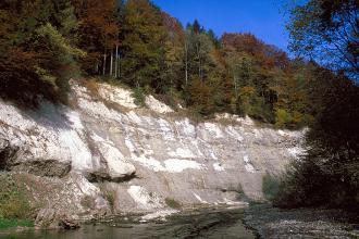 Am linksseitigen Ufer eines schmalen Flusses erhebt sich eine hohe, lange Felsböschung. Der Fels ist grau mit weißen Flecken und teils glatt, teils hervorstehend. Die Kuppe der Böschung ist bewaldet.