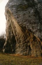 Das Bild zeigt einen hoch aufragenden, dunkelgrauen Felsen, an dessen linker Seite eine abgeschrägte, rötlich graue Nische zu sehen ist.