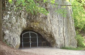 Das Bild zeigt den mit einer Gittertür verschlossenen halbrunden Eingang zu einer Höhle am Fuß einer steil aufragenden Felswand. Zum Eingang führt ein geebneter Weg.