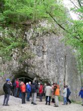 Blick auf eine senkrecht aufragende, graue Felswand, die im oberen Bereich bemoost und mit Bäumen bewachsen ist. Am Fuß der Felswand ist der vergitterte Eingang zu einer Höhle erkennbar. Eine Besuchergruppe wartet vor dem Höhleneingang.