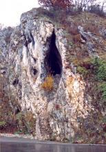 Blick auf eine steil aufragende Felsformation, deren rechte Flanke von Moos, Sträuchern und Bäumen bewachsen ist. Im hellen Mittelteil klafft die spitz zulaufende Öffnung einer Höhle. Eine Steintreppe führt aufwärts zum Eingang. Vorne fließt ein Fluß.