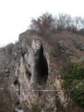 Inmitten eines auf der Kuppe sowie der rechten Seite bewachsenen Felsenhanges öffnet sich eine schmale, hohe Höhle. Eine Treppe führt hinauf zum Eingang. Auf der linken Seite der bleichen Felswand sind weitere, kleinere Höhlen und Nischen erkennbar.