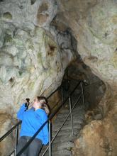 Blick auf einen durch Steintreppen erschlossenen Höhlengang, dessen Decke oben scheinbar zusammenläuft. Links wird die Höhlenwand von einer Besucherin mit Taschenlampe beleuchtet.