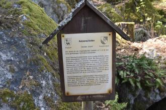Blick auf eine überdachte Holztafel mit wissenswerten Informationen zum Katzenschrofen, einer Felsformation im Hintergrund.