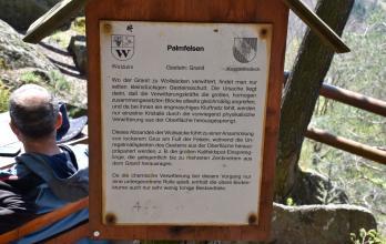 Blick auf eine Holztafel mit Informationen zum Palmfelsen. Der Fels besteht aus Granit und ist zu sogenannten Wollsäcken verwittert.