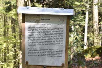 Blick auf eine mit Blech überdachte Holztafel. Die Tafel enthält Wissenswertes zum Spitzfelsen, der aus Porphyr besteht. Die Tafel befindet sich vor einem Wald.