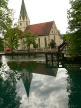 Eine schlichte, mit einem spitzen Turm versehene Kirche spiegelt sich in einer unmittelbar angrenzenden Wasserfläche.