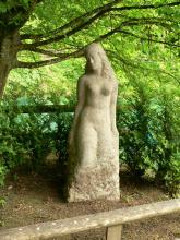 Auf dem Bild sieht man die aus einem hellen Steinblock modellierte Skulptur einer Frau. Die Skulptur steht im Schatten eines Baumes und ist von Sträuchern umgeben.