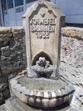 Im Eck einer Steinmauer steht ein ebenfalls aus Stein gefertigter Brunnen. Das Wasser, das aus einer froschartigen Figur fließt, gelangt in ein halbrundes, teilweise überlaufendes Becken.