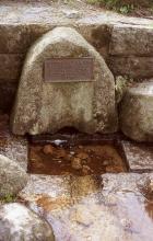 Ein halbrunder, olivbrauner und mit einer Tafel versehene Stein lehnt an einer Mauer. Vor dem Stein ist eine rechteckige Vertiefung, die mit Wasser gefüllt ist. Dieses Wasser fließt über eine Rinne auf den Betrachter zu.