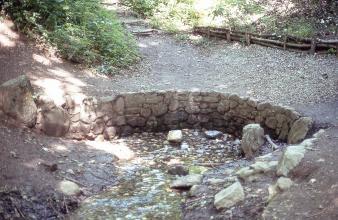 Blick auf eine kleine, von einem niedrigen Steinbogen eingefasste Wasserquelle. Im Hintergrund führen hölzerne Stufen einen Waldhang hinauf.