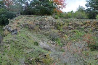 Blick auf einen mit trockenem Gras und Sträuchern bewachsenen, oben abgeflachten Hügel. Links am Rand und unterhalb der Kuppe ist in einem kleinen Bereich graues Gestein aufgeschlossen. In der Bildmitte ist eine Mulde im Hügel erkennbar.