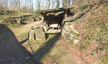 Blick von erhöhtem Standpunkt auf im Boden verlegte Gleise für Loren. Rechts erhebt sich ein steiler Hang, den unten eine Steinmauer stützt. Ein hölzerner Unterstand ist daran angebaut. Links folgt treppenartiges Gelände und Wald.