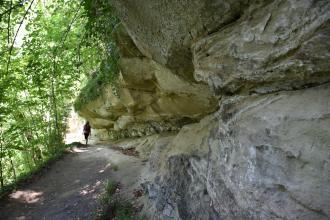 Das Bild zeigt rechts mächtiges, teils wie ein Dach überhängendes gelblich graues Felsgestein. Links, an der Felsformation entlang, verläuft ein schmaler, von Bäumen gesäumter Wanderweg.