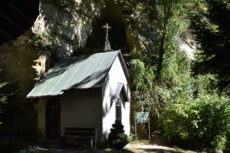 Blick auf eine kleine Kapelle, die vor einer links aufsteigenden hohen Felswand steht. Die Kapelle ist weiß mit grauem Dach. Rechts stehen Bäume und Büsche. Von links her fallen tiefe Schatten auf Felsen und Kapelle.