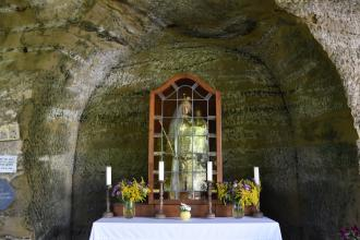 Das Bild zeigt eine in einer bogenförmigen Felsnische gelegene Andachtsstätte. Auf einem mit weißem Tuch bedeckten Tisch sind Kerzen sowie eine hinter Glas und Holz befindliche Marienfigur aufgestellt.