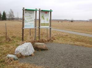 Das Bild zeigt eine von braunem Gras bedeckte Ebene mit einem querenden Weg. An einem geschotterten Platz stehen in der linken Bildhälfte zwei größere Hinweistafeln. Davor liegen ein großer weißer und ein kleinerer brauner Felsblock.