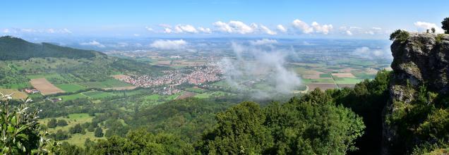 Aus großer Höhe blickt man in diesem Panoramabild auf eine weite Landschaft mit Feldern, Wäldern und Siedlungen. Rechts erhebt sich eine markante, vorspringende Felsengruppe als Aussichtspunkt. Links im Mittelgrund befindet sich ein bewaldeter Bergrücken.