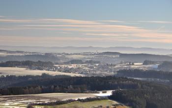 Blick von erhöhtem Standort über eine hügelige, leicht verschneite Landschaft mit Siedlungen und größeren Waldgebieten. Am Horizont ist eine langgestreckte Bergkette erkennbar.