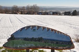 Blick auf zum Hintergrund hin abfallende, verschneite Äcker.  Eine Häuserzeile begrenzt die Äcker. Dahinter folgen bewaldete Berge und Hügel. Im Vordergrund steht eine Orientierungstafel, die Landschaft zeigt sich darauf im Sommerkleid.