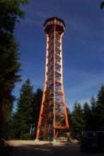 Auf einer kleinen Waldlichtung steht ein von hölzernen Strebepfeilern gestützter Aussichtsturm. In der Turmmitte verläuft eine Aufstiegstreppe. Oben ist eine überdachte Kanzel angebracht.