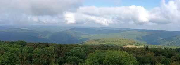 Vom Aussichtsturm auf dem Katzenbuckel geht der Blick über ausgedehnte Waldflächen und bewaldete Berge. Im dunstigen und wolkigen Hintergrund ist links der Bildmitte ein Steinbruch und rechts ein Sendeturm zu erkennen.