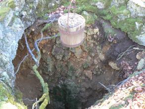 Blick in eine tiefe Grube mit unregelmäßigem Rand und oben hängendem Förderkorb.