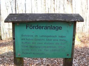 Grüne, an zwei Holzpfosten angebrachte Informationstafel, die auf eine ehemalige Förderanlage von Erzen hinweist.