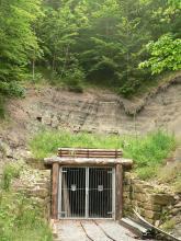 Das Bild zeigt den vergitterten Eingang zu einem von Steinbruchwänden umgebenen Stollen.