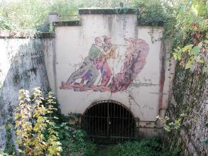 Blick auf ein altes Stollenportal mit vergittertem Eingang und farbigem Fresko, das Bergbauarbeiter zeigt.
