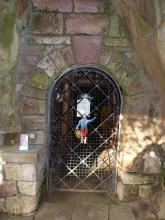 Blick auf den mit einer Gittertür verschlossenen Eingang eines Bergwerks.