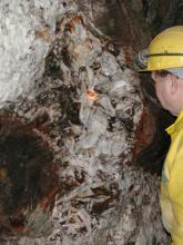 Blick auf die weiß und braun marmorierte Stollenwand eines Bergwerks.