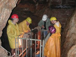 Das Bild zeigt Mitarbeiter und Besucher eines Bergwerks, die eine Seilwinde mit Förderkorb betrachten.